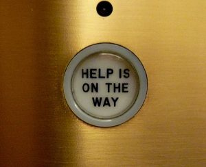 "Elevator button saying ""HELP IS ON ITS WAY"""