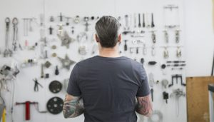 Tattooed helicopter mechanic looking at tools on wall